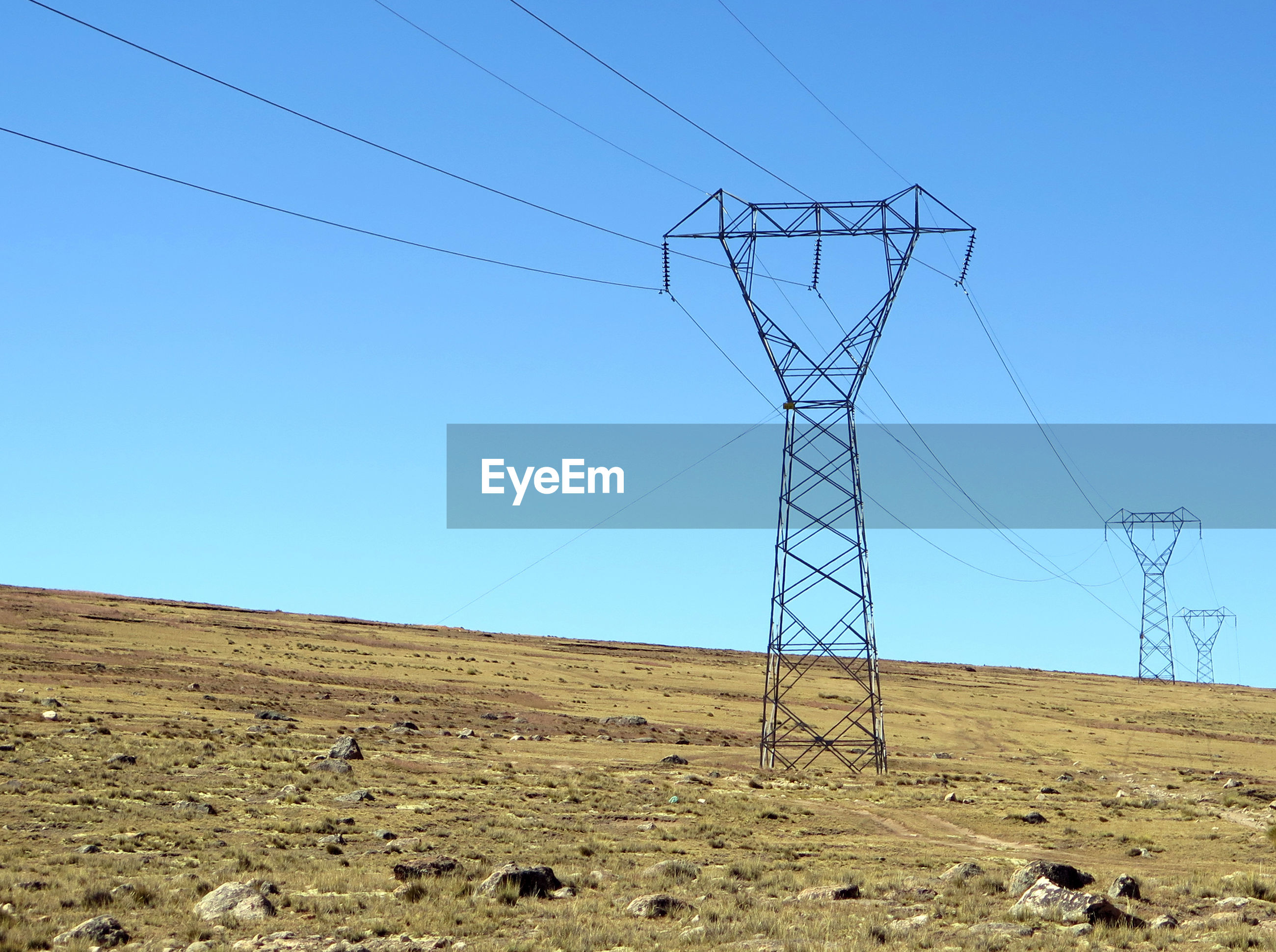 Low angle view of electricity pylons on field against clear blue sky