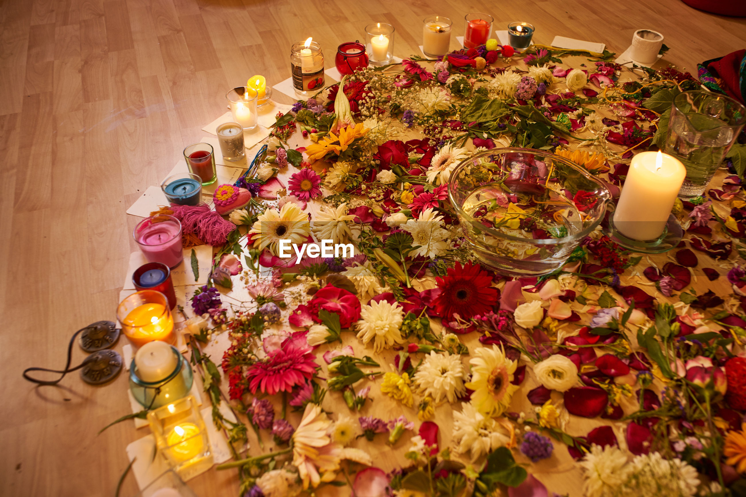 High angle view of various flowers and candles on floor