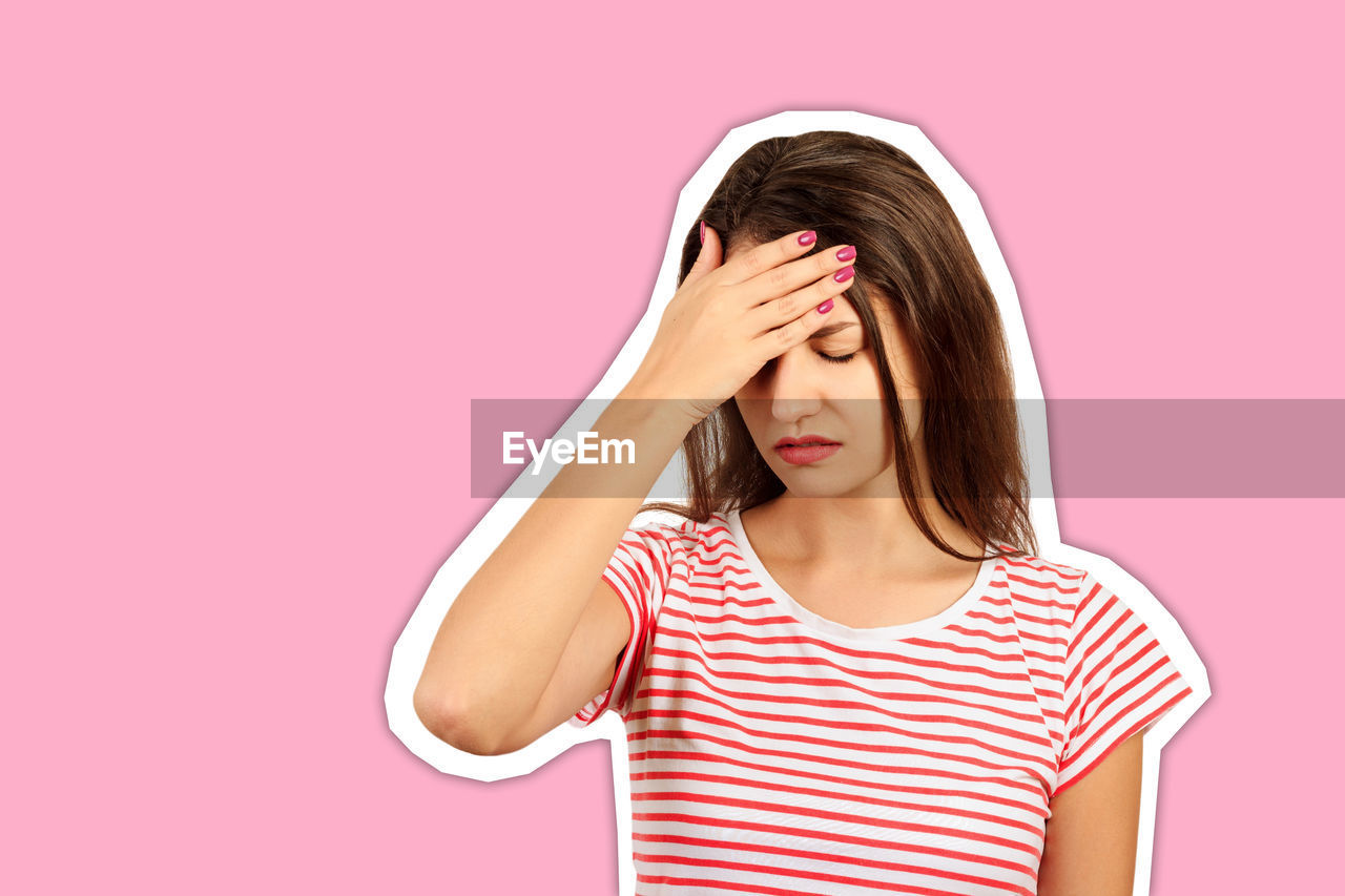 Young woman with head in hands against pink background