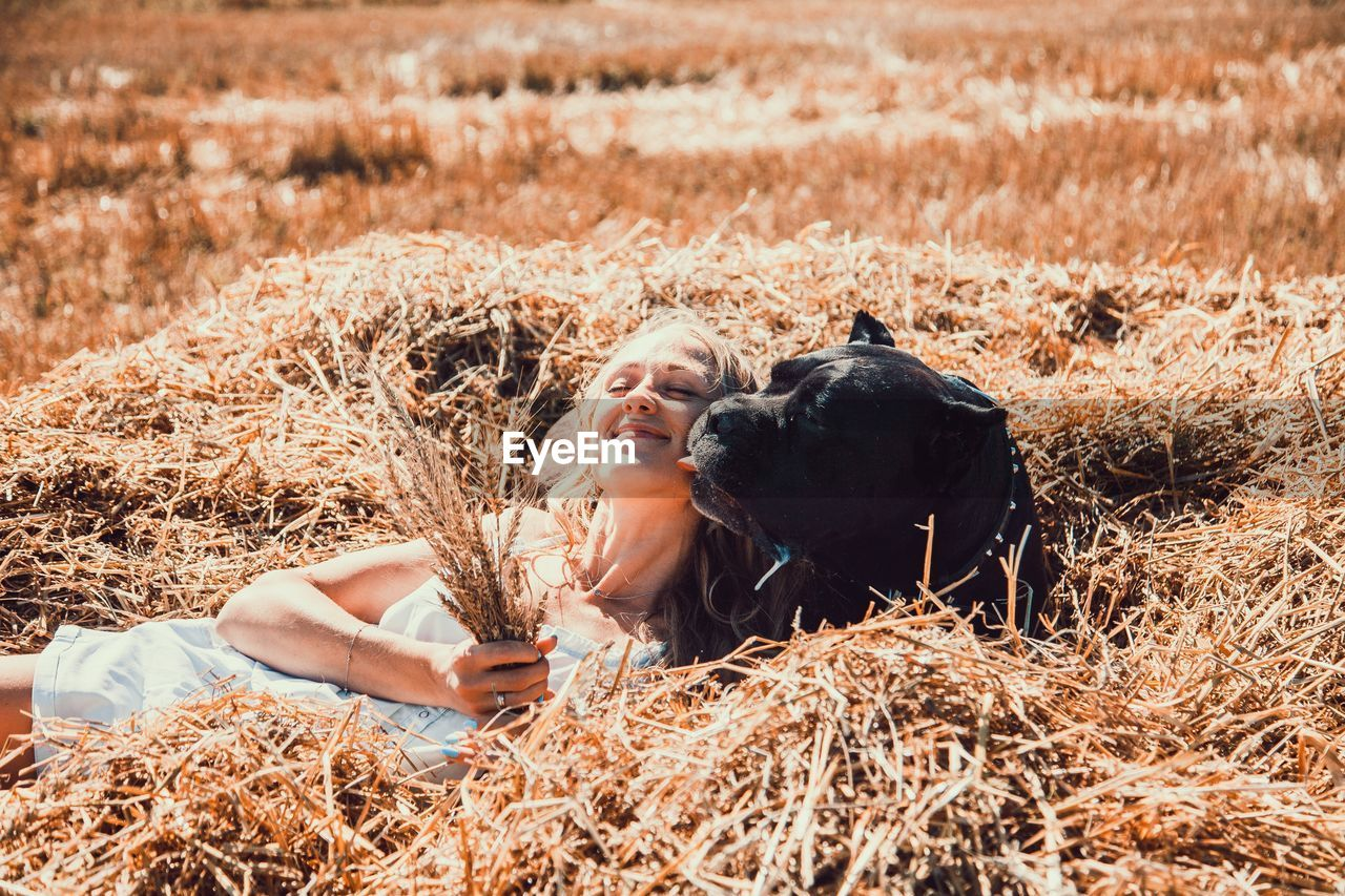 Woman with dog relaxing on hay
