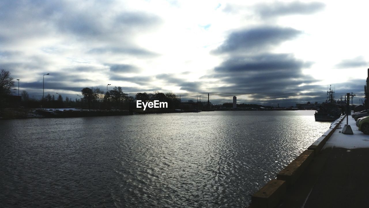 River By Parking Lot Against Cloudy Sky