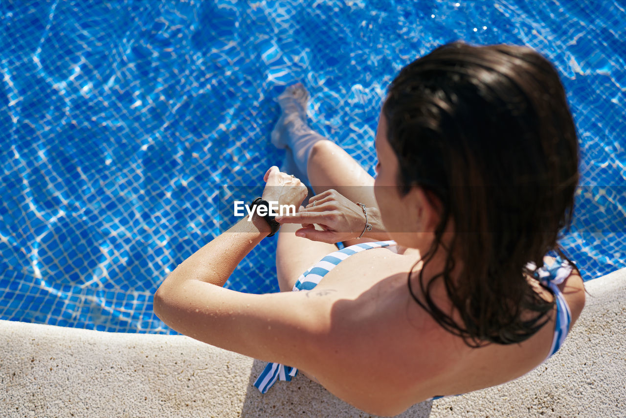High angle view of woman relaxing in swimming pool