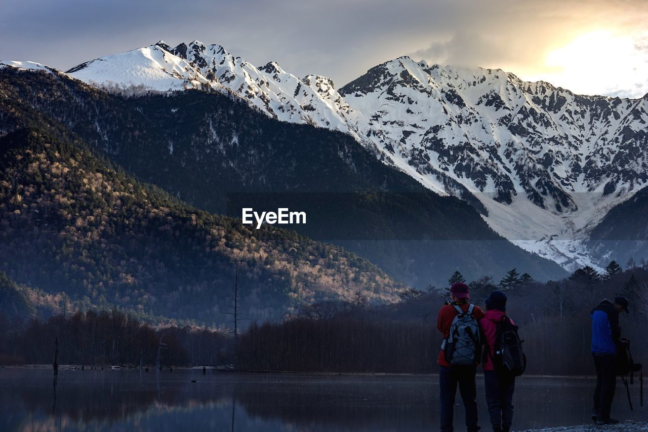 mountain, scenics - nature, beauty in nature, cold temperature, mountain range, winter, sky, snow, real people, tranquil scene, two people, nature, leisure activity, non-urban scene, tranquility, men, snowcapped mountain, rear view, lake, outdoors, mountain peak