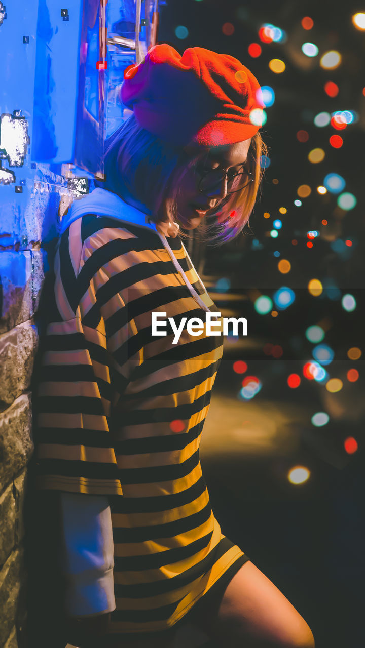 one person, illuminated, lifestyles, real people, women, celebration, leisure activity, three quarter length, night, standing, casual clothing, child, girls, childhood, indoors, females, rear view, focus on foreground, glowing, hairstyle