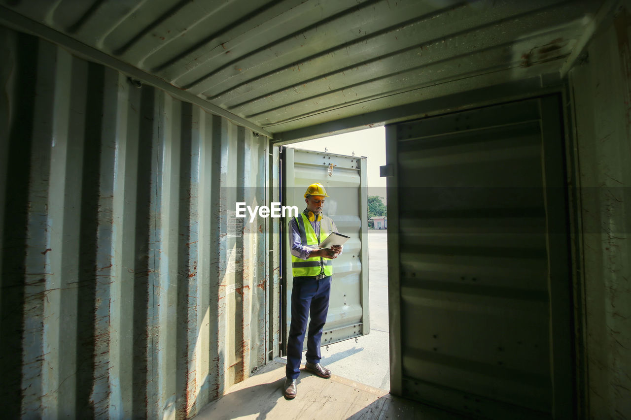 Full length of manual worker holding clipboard standing under cargo container