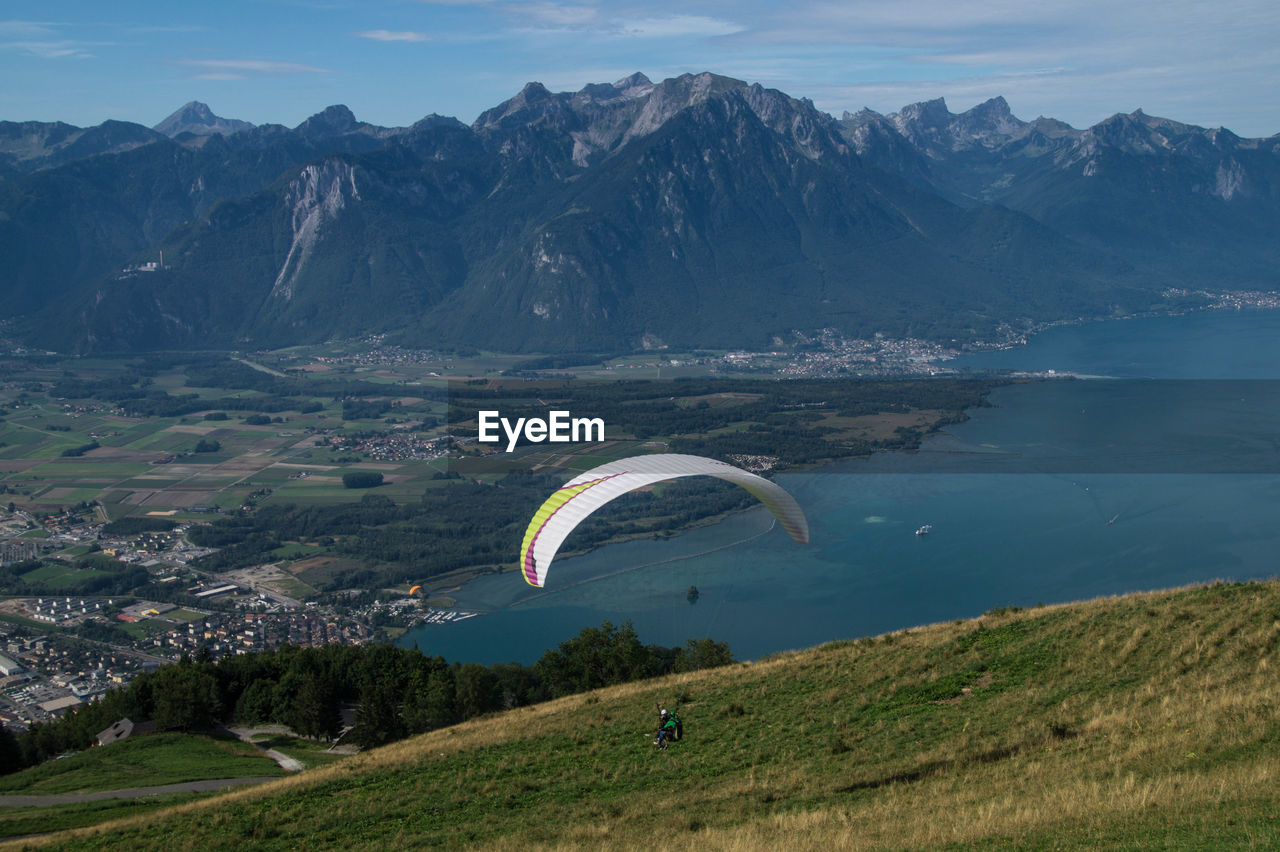 Person Paragliding Against Mountains