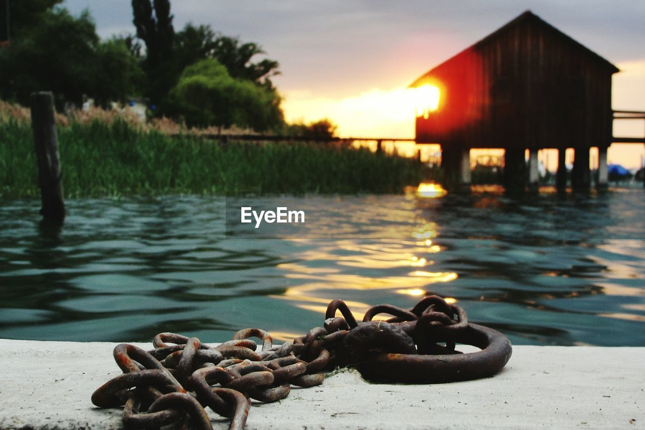 Close-up of rusty chain by lake