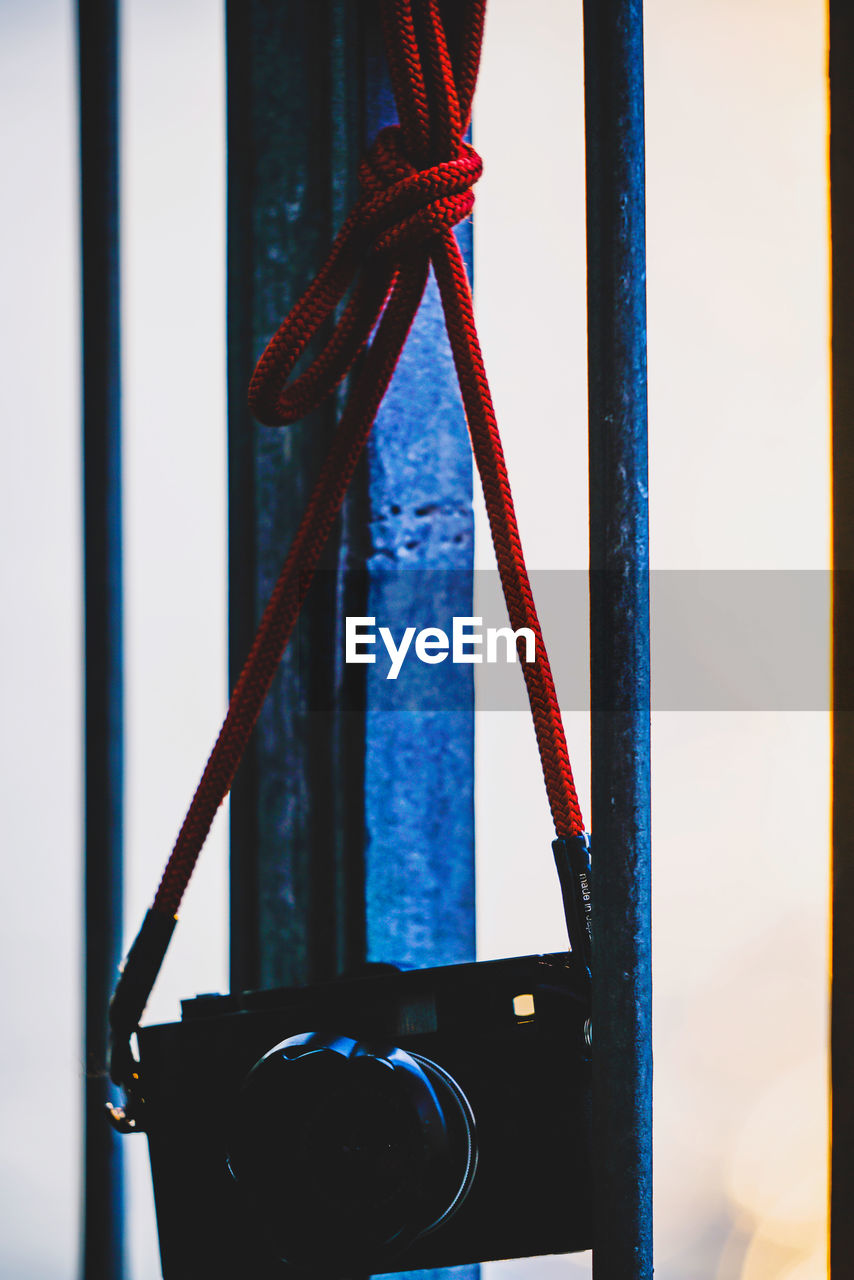 no people, close-up, hanging, indoors, focus on foreground, red, wall - building feature, metal, day, window, still life, rope, equipment, blue, transparent, built structure, pole, sport, shape