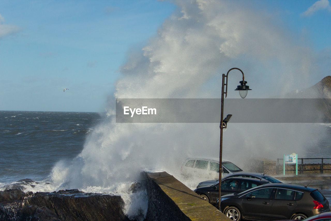 VIEW OF WAVES BREAKING AGAINST SEA