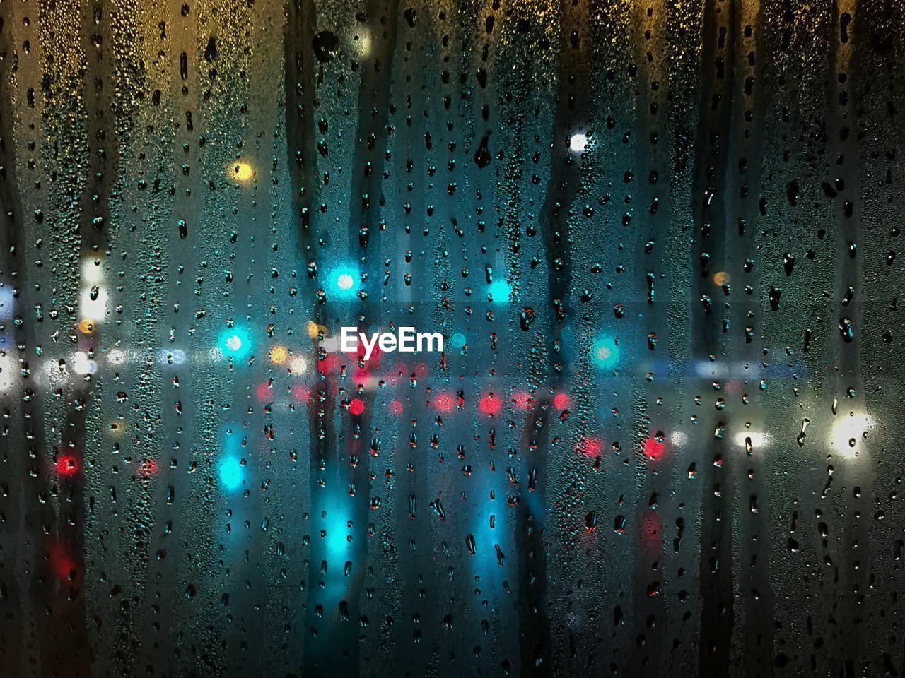 Illuminated lights seen through wet window during rainy season