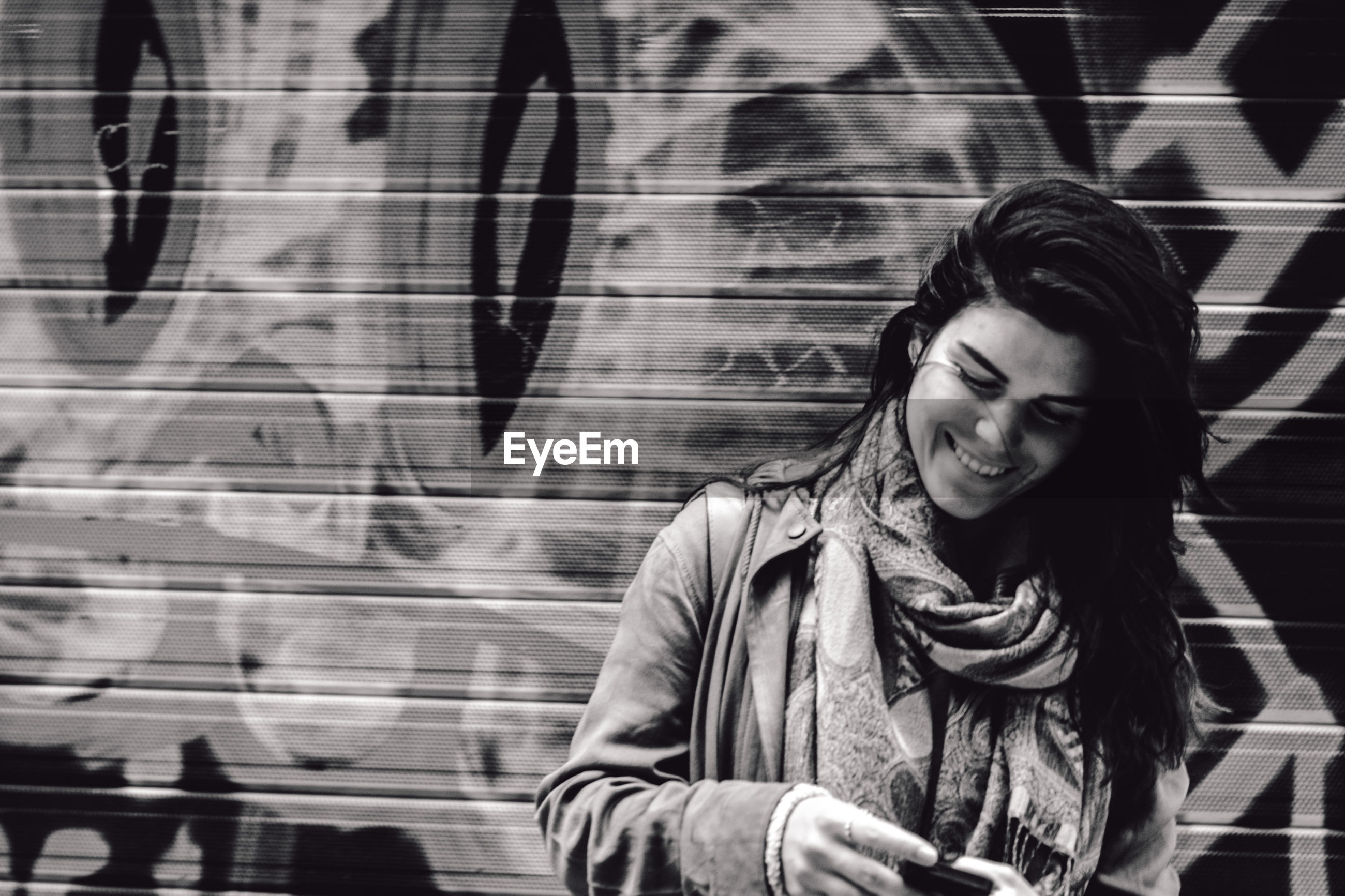 Close-up of happy woman using phone while standing by graffiti wall