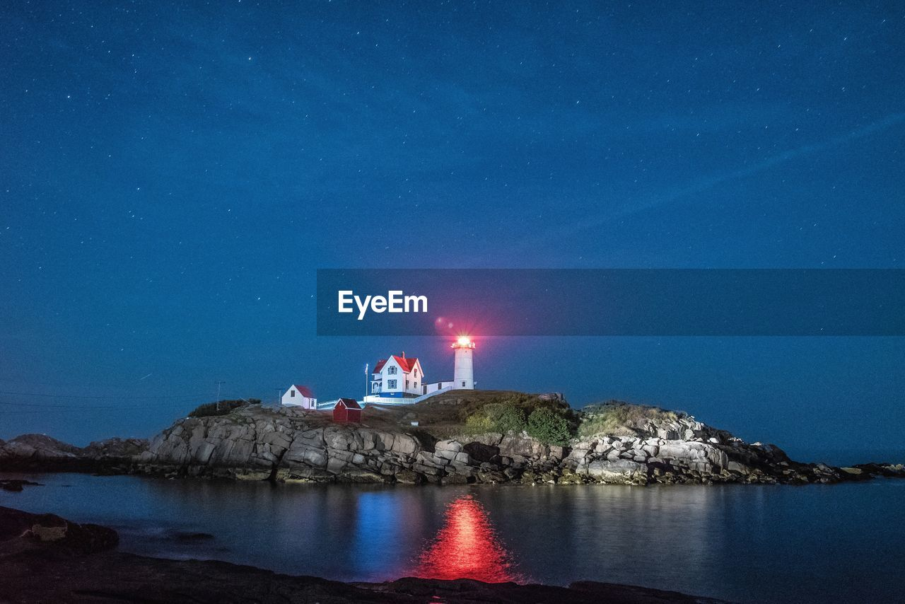 Illuminated Nubble Lighthouse By Sea Against Star Field