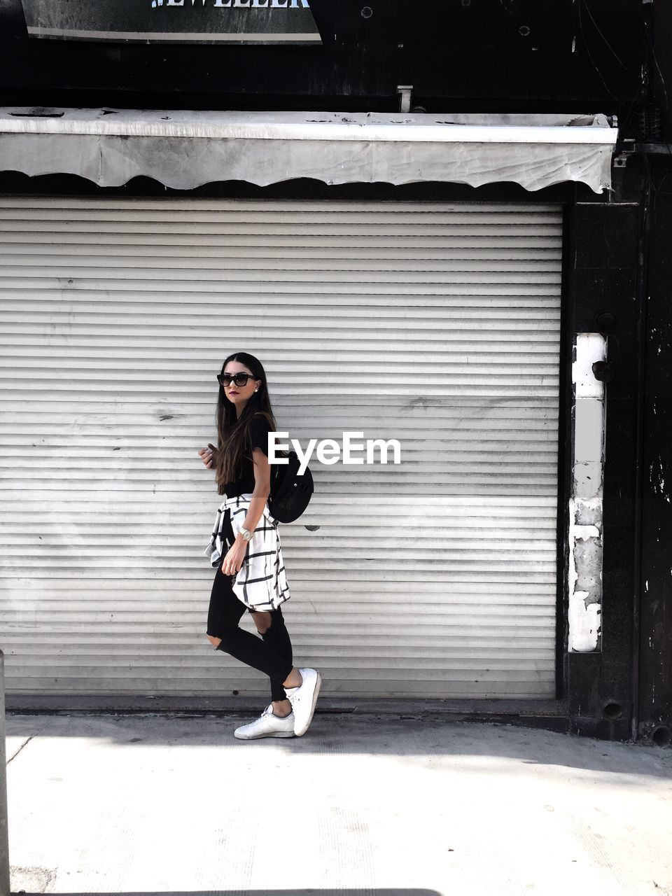 Side View Of Woman Standing On Footpath Against Shutter