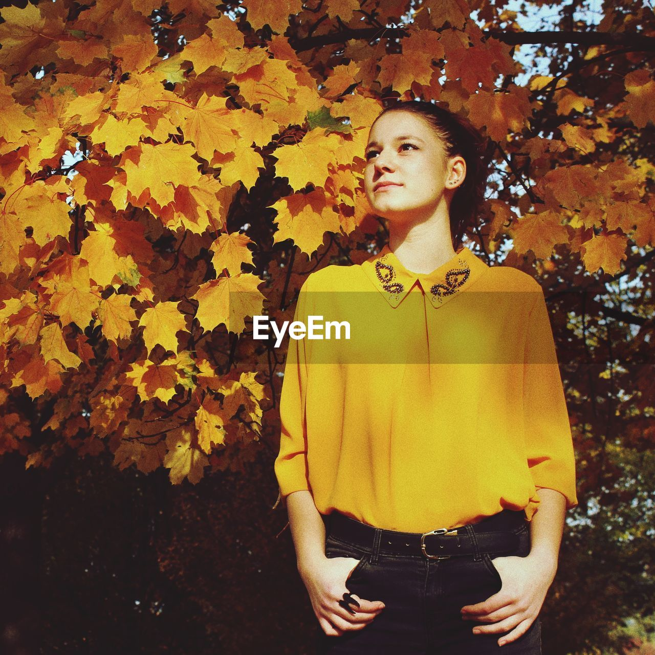 Thoughtful young woman standing by autumn tree