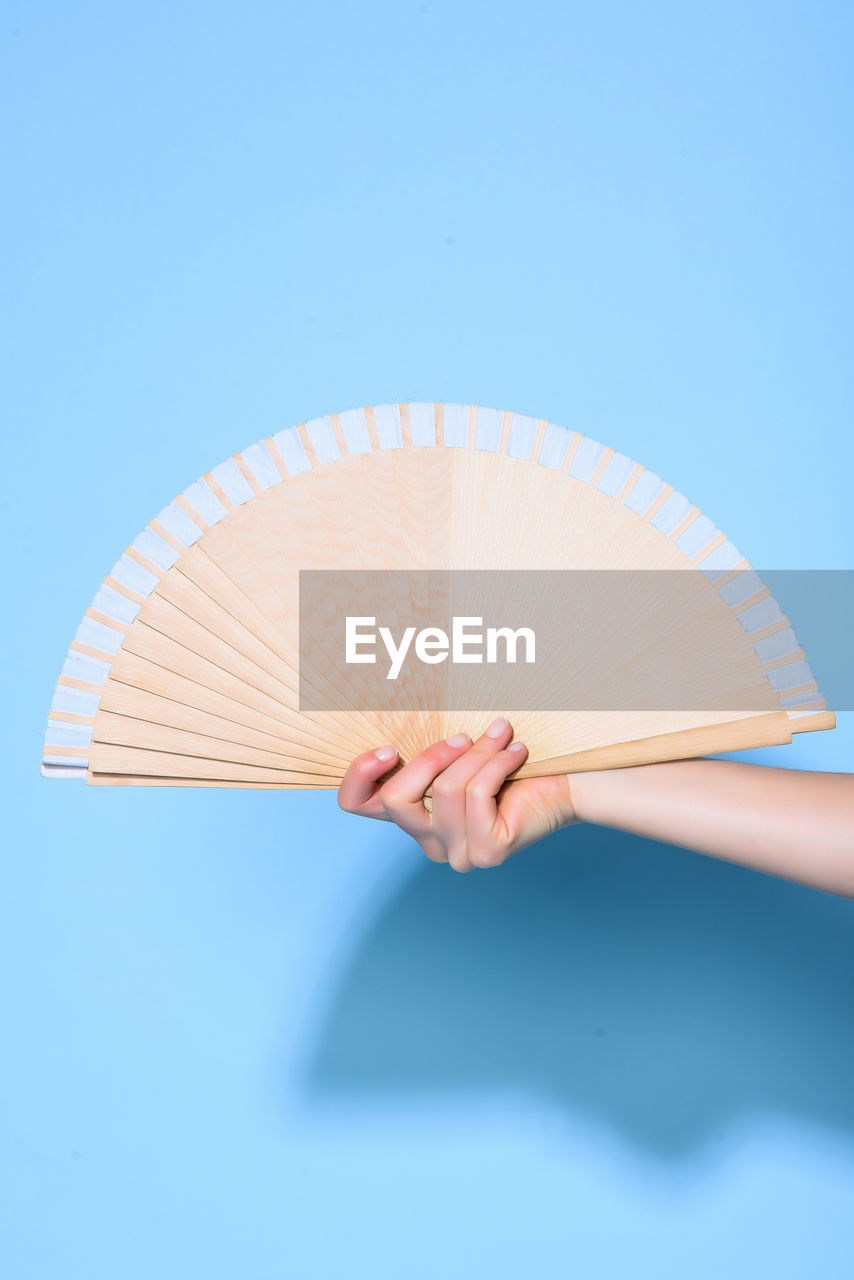 Close-Up Of Woman Holding Hand Fan Against Blue Wall
