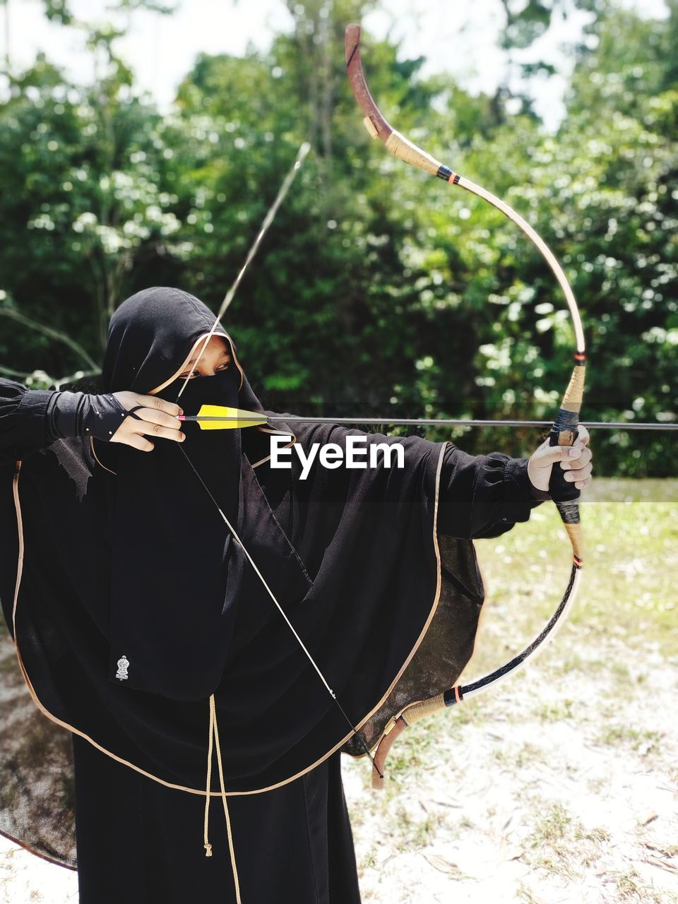 Woman Aiming With Archery On Field