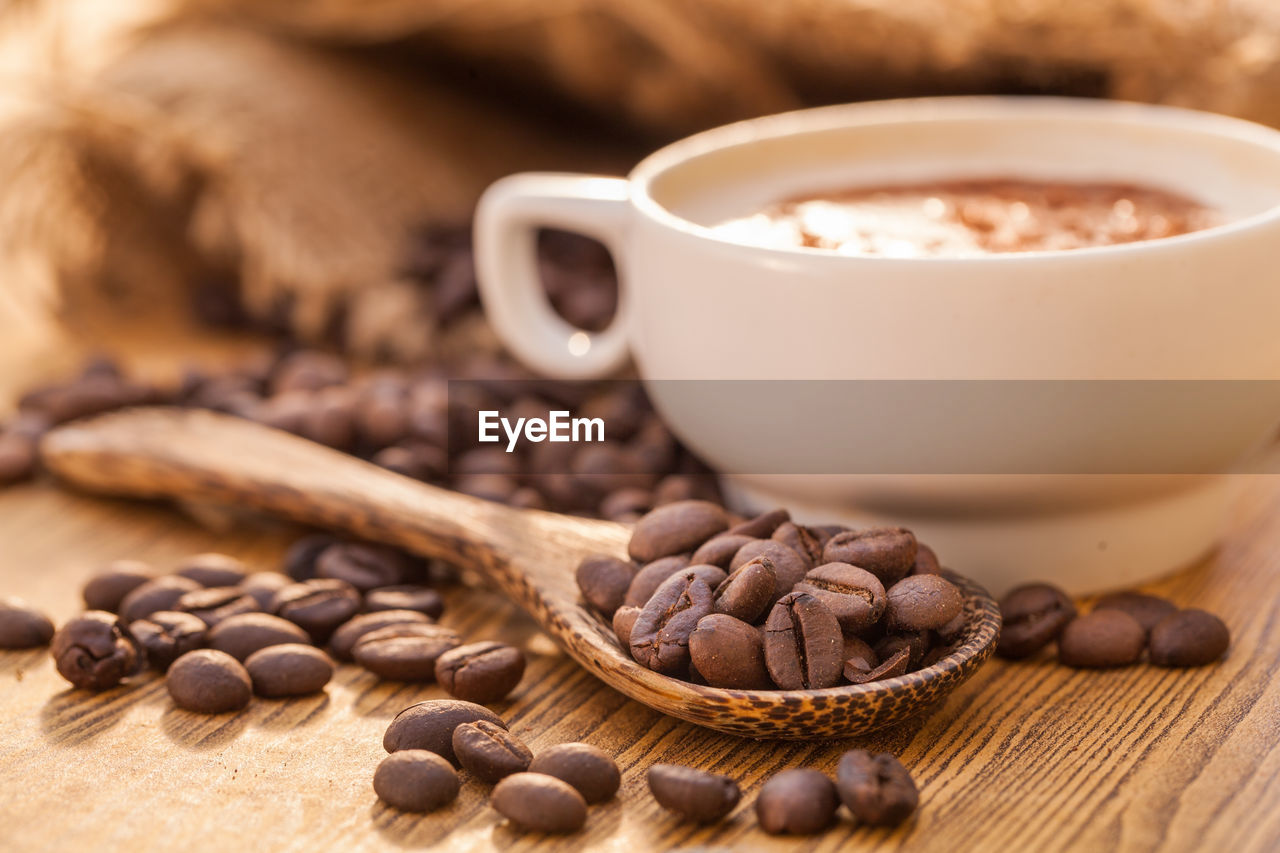 food and drink, food, coffee - drink, coffee, cup, table, still life, mug, freshness, coffee cup, brown, roasted coffee bean, spoon, wood - material, close-up, refreshment, kitchen utensil, eating utensil, drink, indoors, no people, crockery, wooden spoon, caffeine
