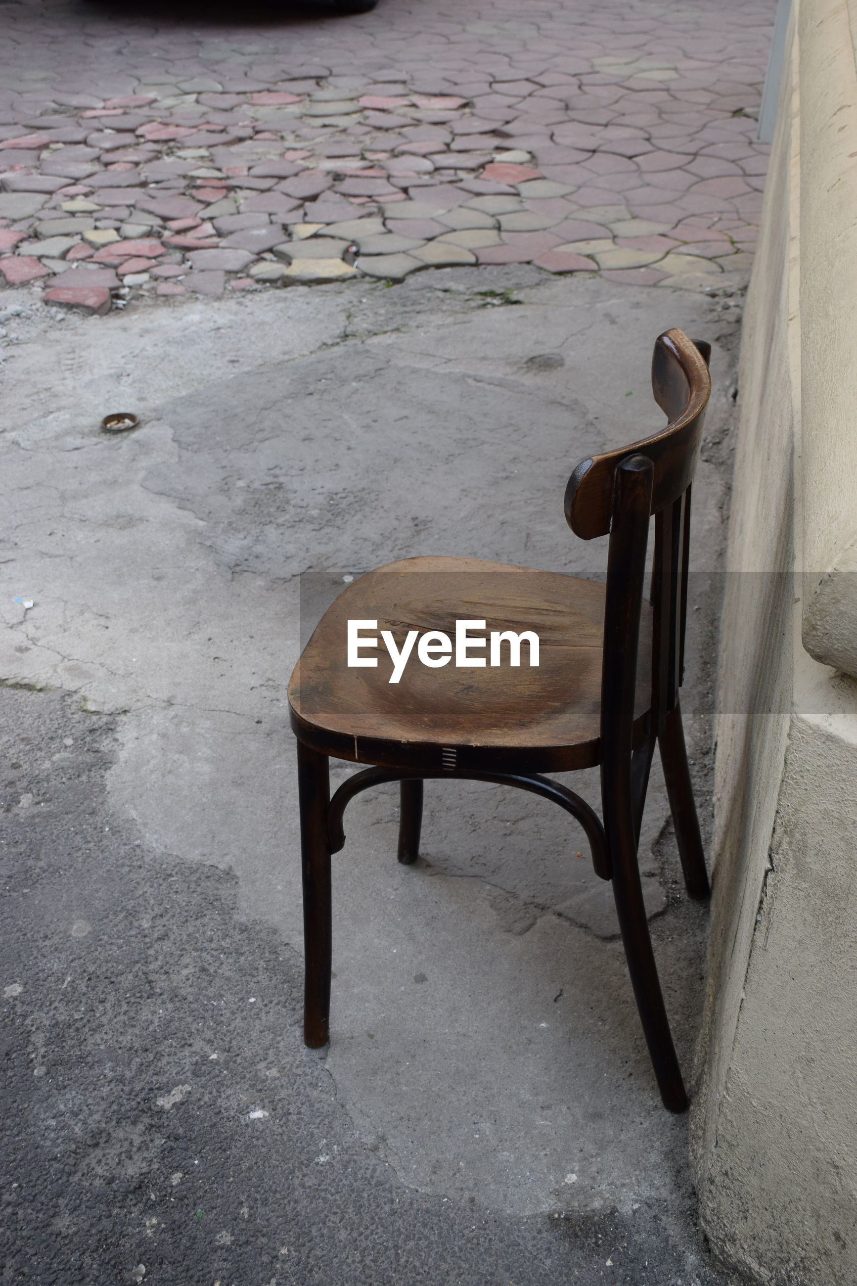 High angle view of old wooden chair on sidewalk
