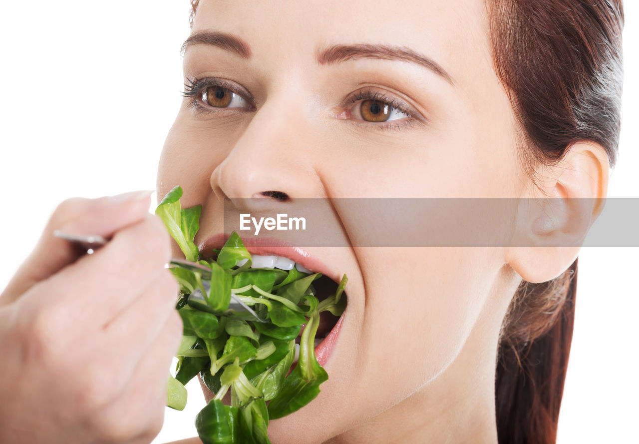 Close-up of woman eating vegetable against white background