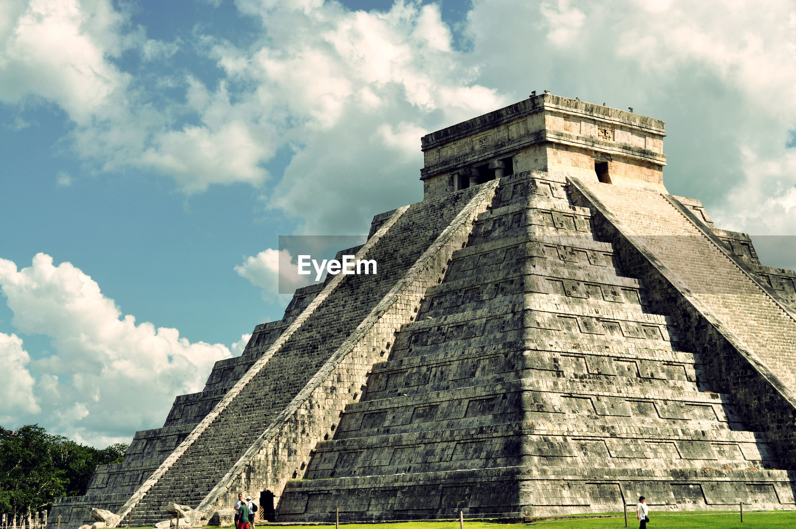 Low angle view of chichen itza against cloudy sky