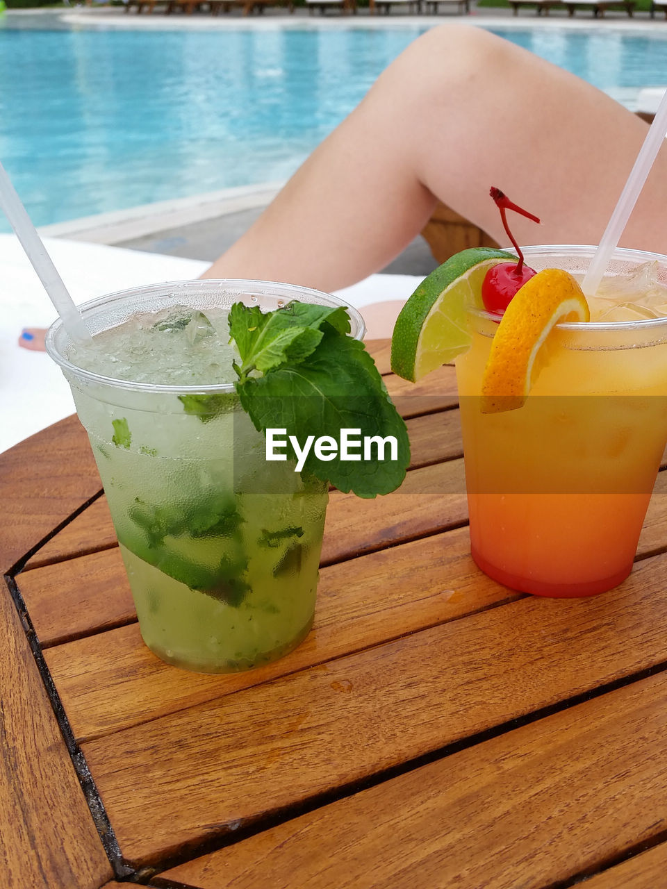 Cocktails on wooden table with swimming pool in background