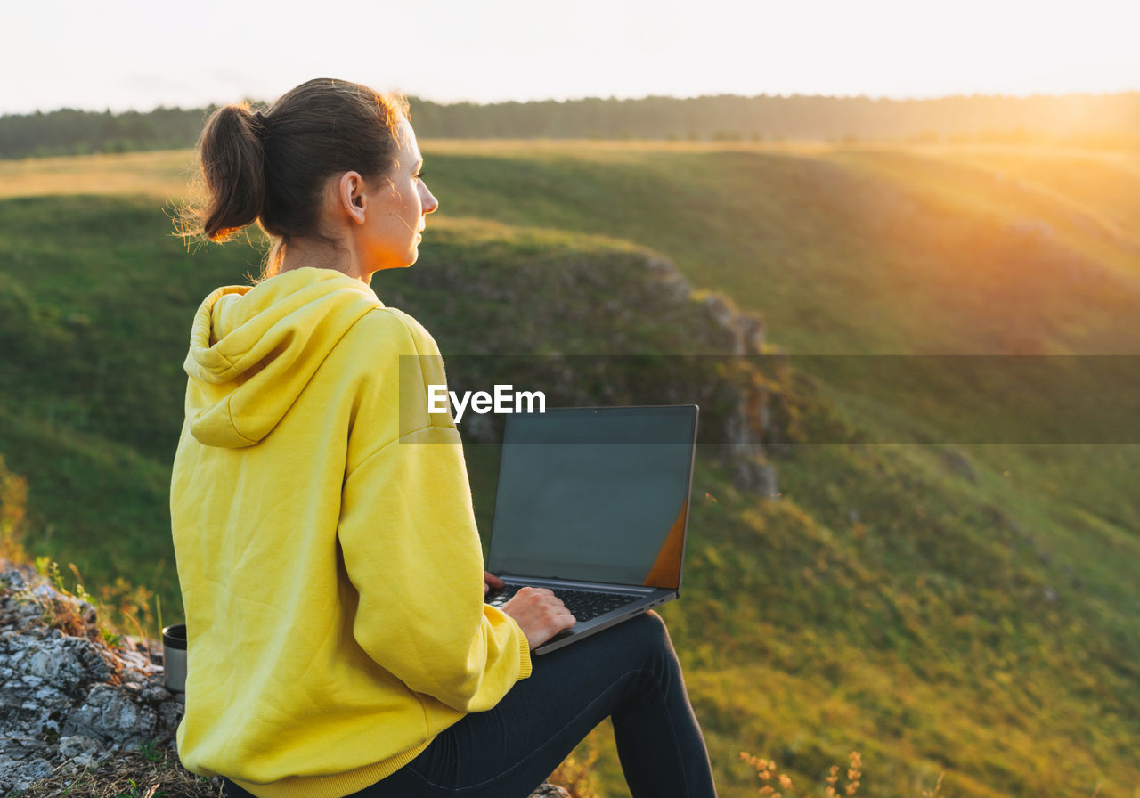 Young woman traveler freelancer in yellow hoodie with opened laptop on beautiful view background