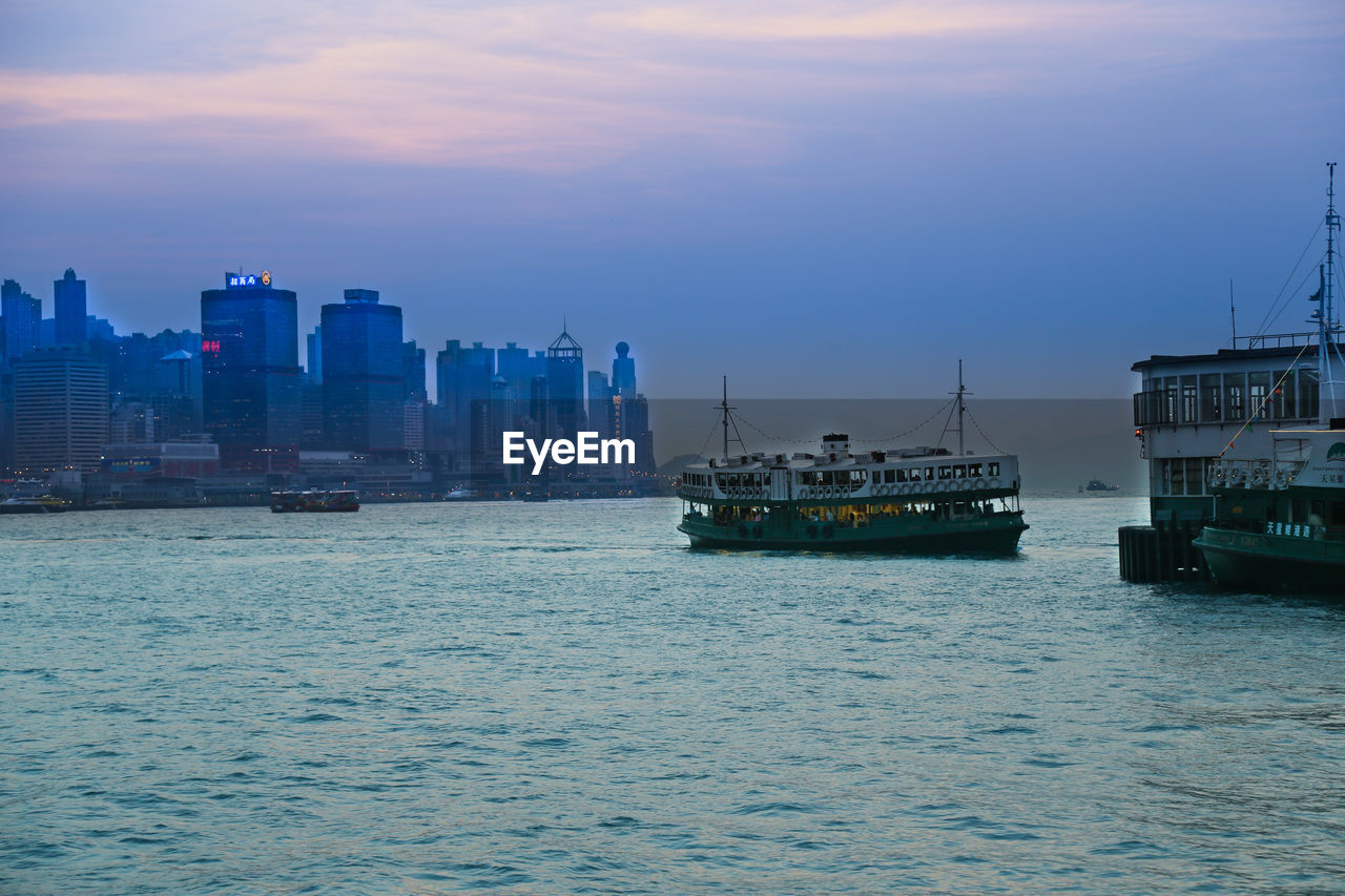 nautical vessel, water, sky, waterfront, architecture, mode of transportation, transportation, building exterior, sea, city, built structure, nature, sunset, no people, cloud - sky, building, ship, outdoors, travel, cityscape, passenger craft, office building exterior, skyscraper