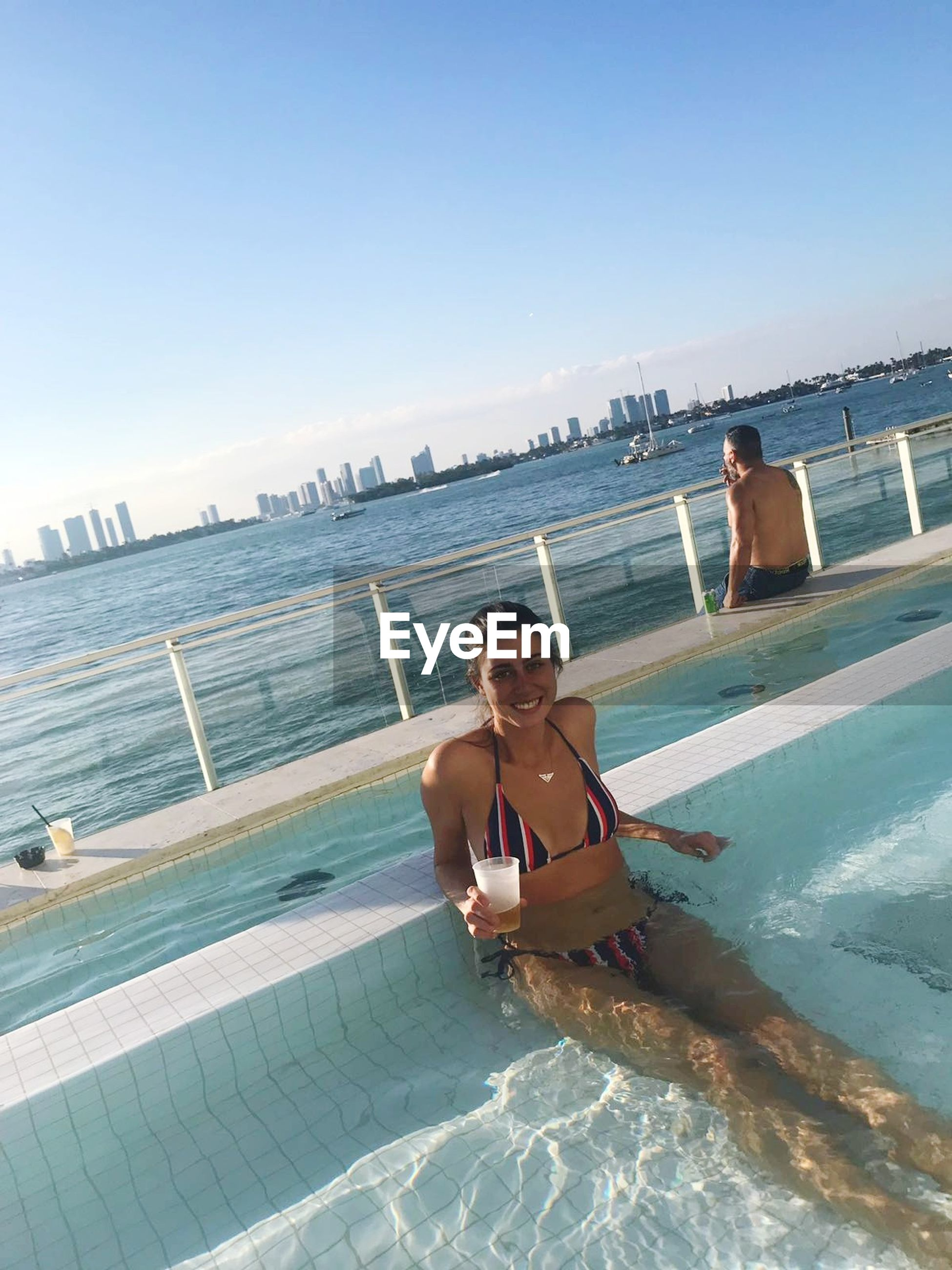 sea, water, two people, young adult, young women, vacations, leisure activity, shirtless, real people, lifestyles, sunlight, beach, outdoors, summer, young men, clear sky, nature, shadow, day, scenics, beauty in nature, swimming pool, full length, men, togetherness, sky, adult, people