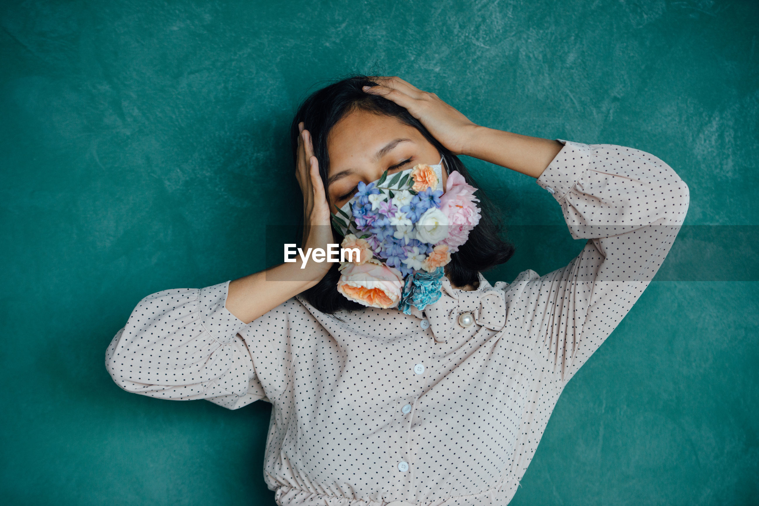 Woman covering mouth with flowers against blue wall