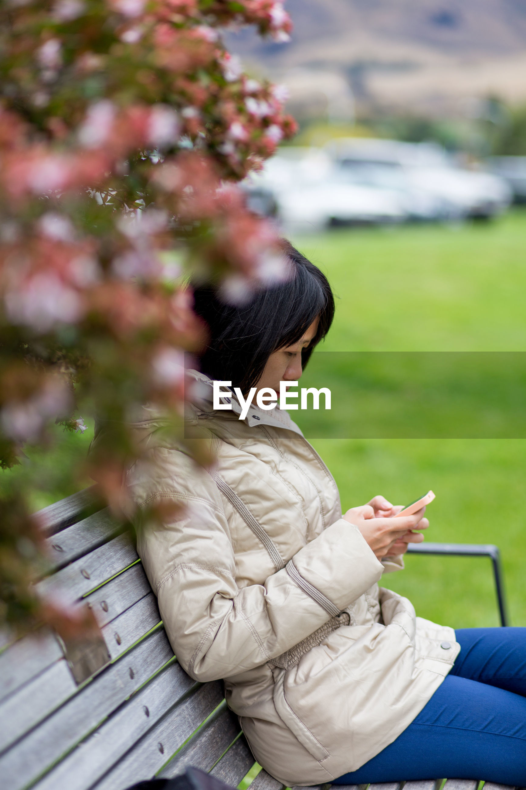Woman using mobile phone while sitting on bench in park