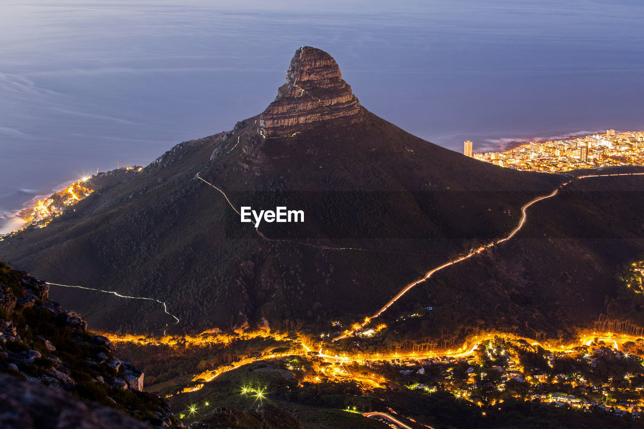 High Angle Shot Of Illuminated Town Against Mountains
