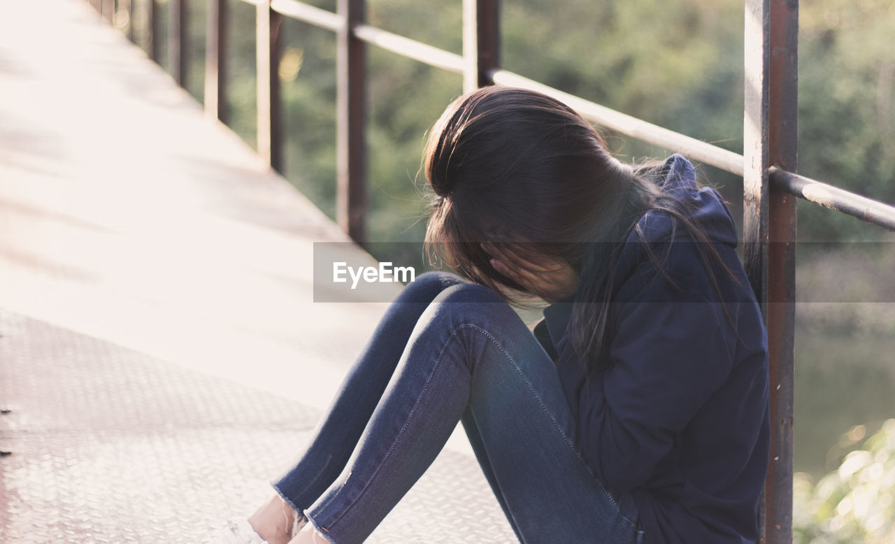Side view of depressed woman covering face while sitting on footbridge