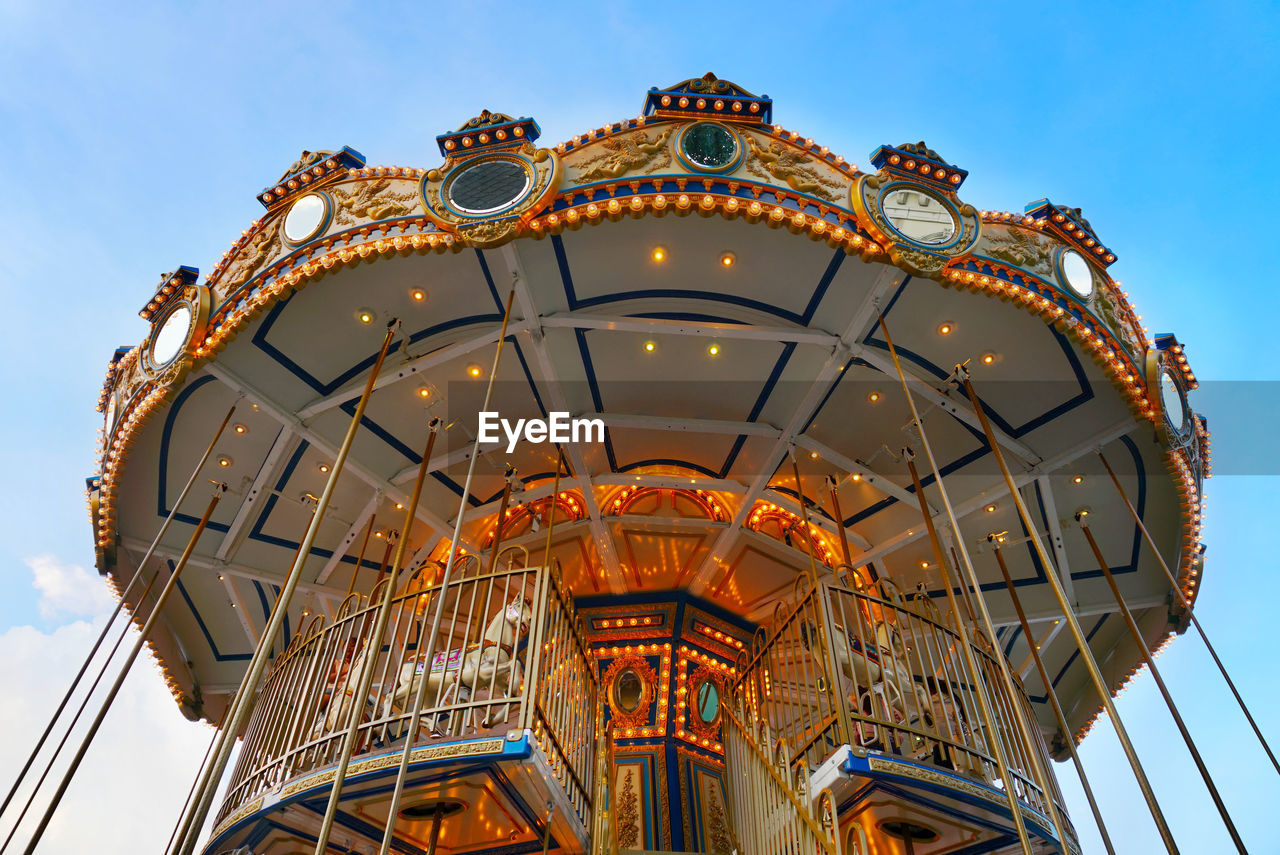 amusement park, amusement park ride, arts culture and entertainment, sky, low angle view, carousel, no people, day, architecture, nature, built structure, leisure activity, outdoors, chain swing ride, merry-go-round, blue, traveling carnival, ferris wheel, enjoyment, cloud - sky, fairground, ornate