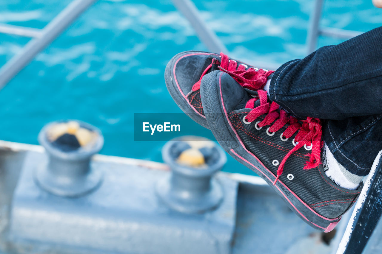 Close-up of person wearing black canvas shoes against blue sea at harbor