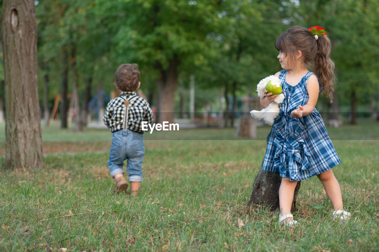 Full Length Of Siblings Playing On Field At Park