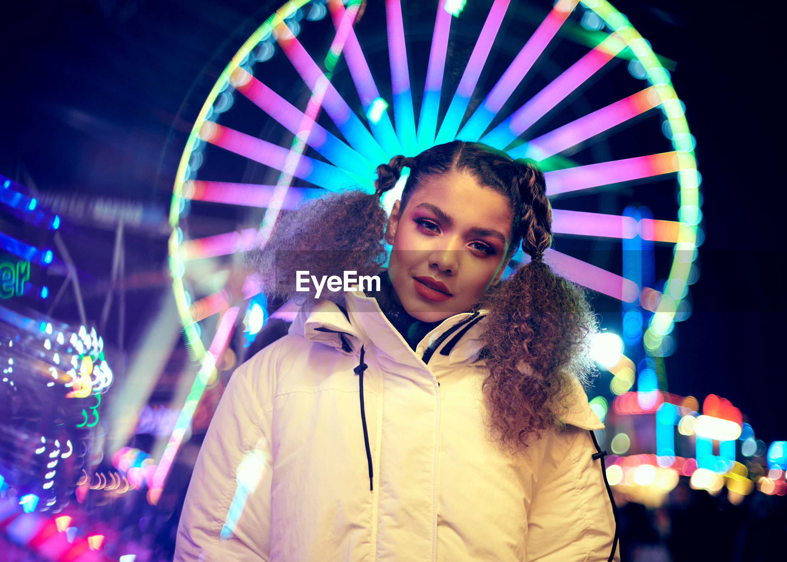 Portrait of smiling woman standing against illuminated ferris wheel at night
