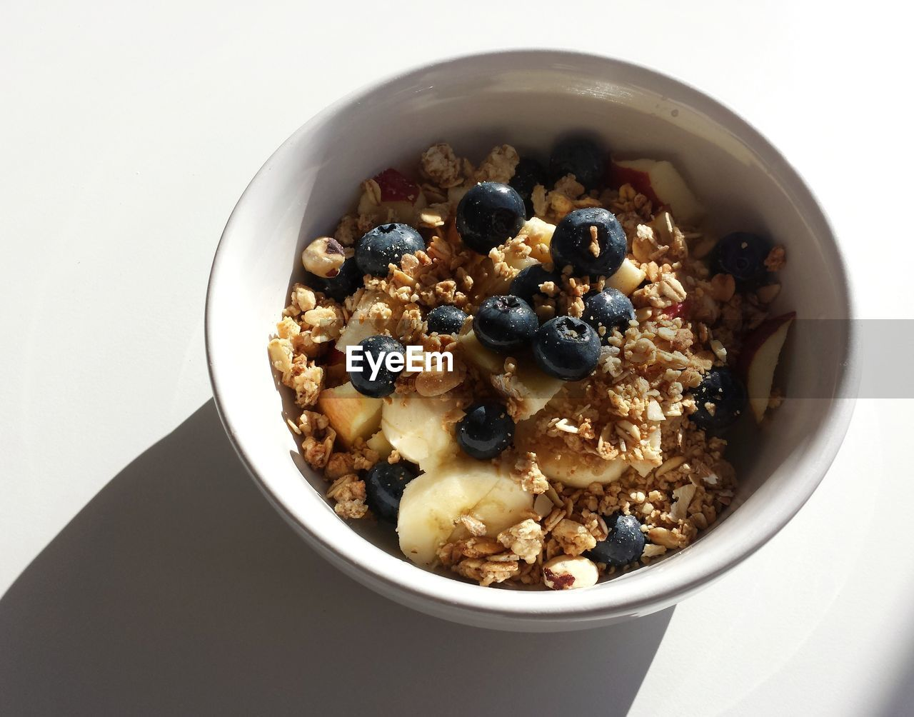 breakfast, bowl, breakfast cereal, healthy eating, blueberry, food and drink, granola, oats - food, freshness, white background, food, fruit, high angle view, milk, corn flakes, no people, indoors, drink, oat flake, studio shot, ready-to-eat, close-up, day