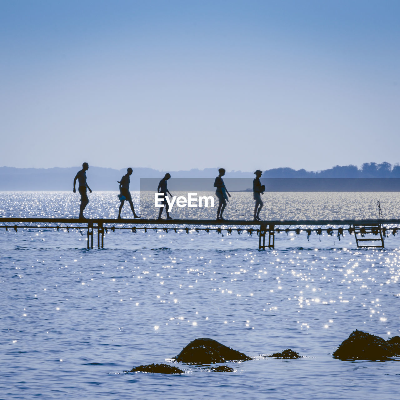 sky, water, real people, group of people, men, clear sky, day, nature, leisure activity, lifestyles, sea, beauty in nature, scenics - nature, copy space, people, sport, land, medium group of people, outdoors