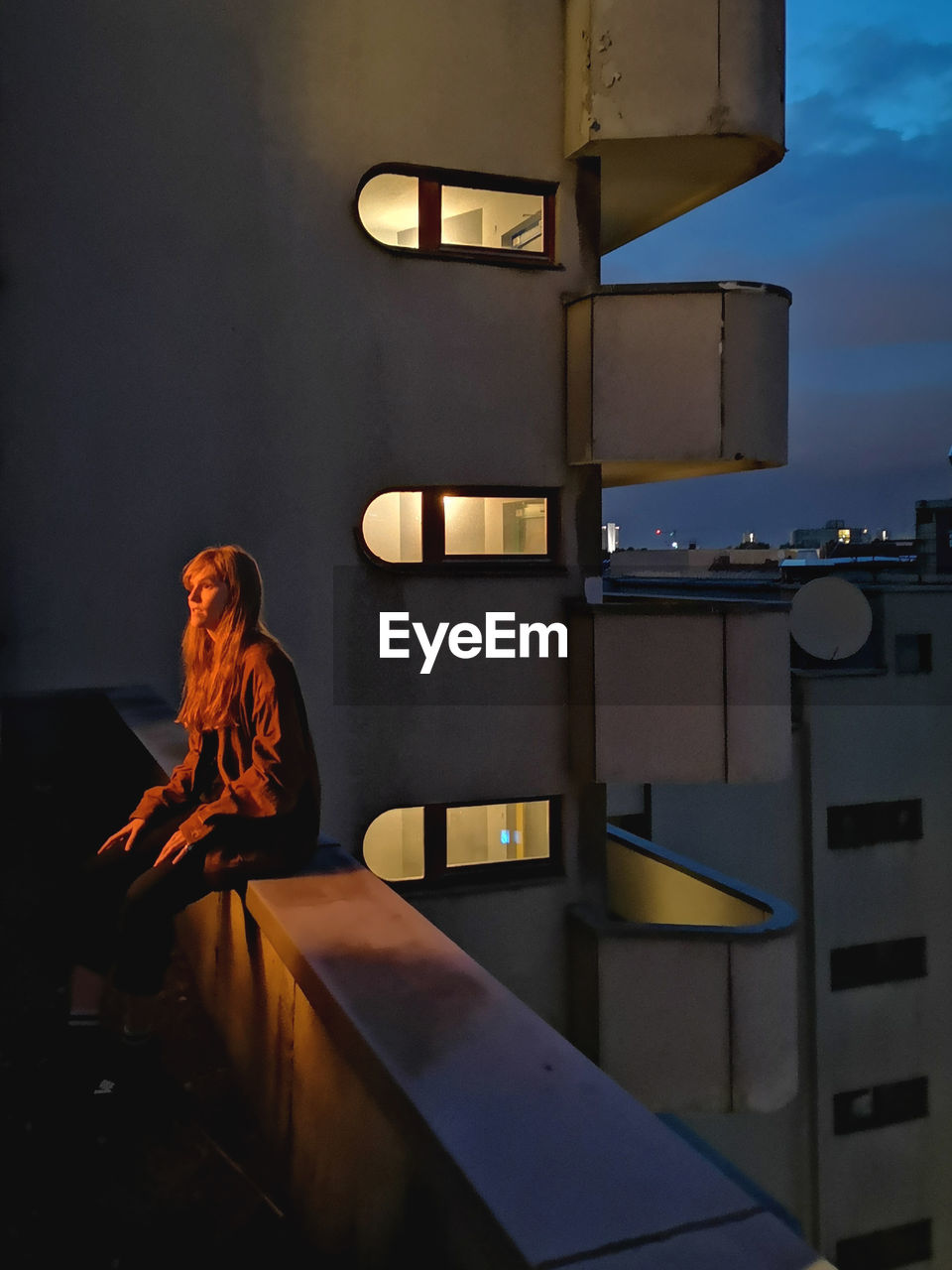 Woman sitting on retaining wall in balcony at night
