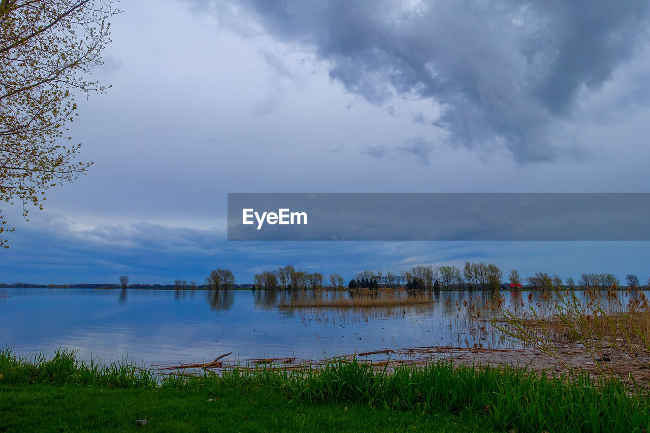 water, lake, sky, cloud - sky, grass, nature, beauty in nature, scenics, tranquility, tranquil scene, outdoors, reflection, day, growth, no people, nautical vessel, tree