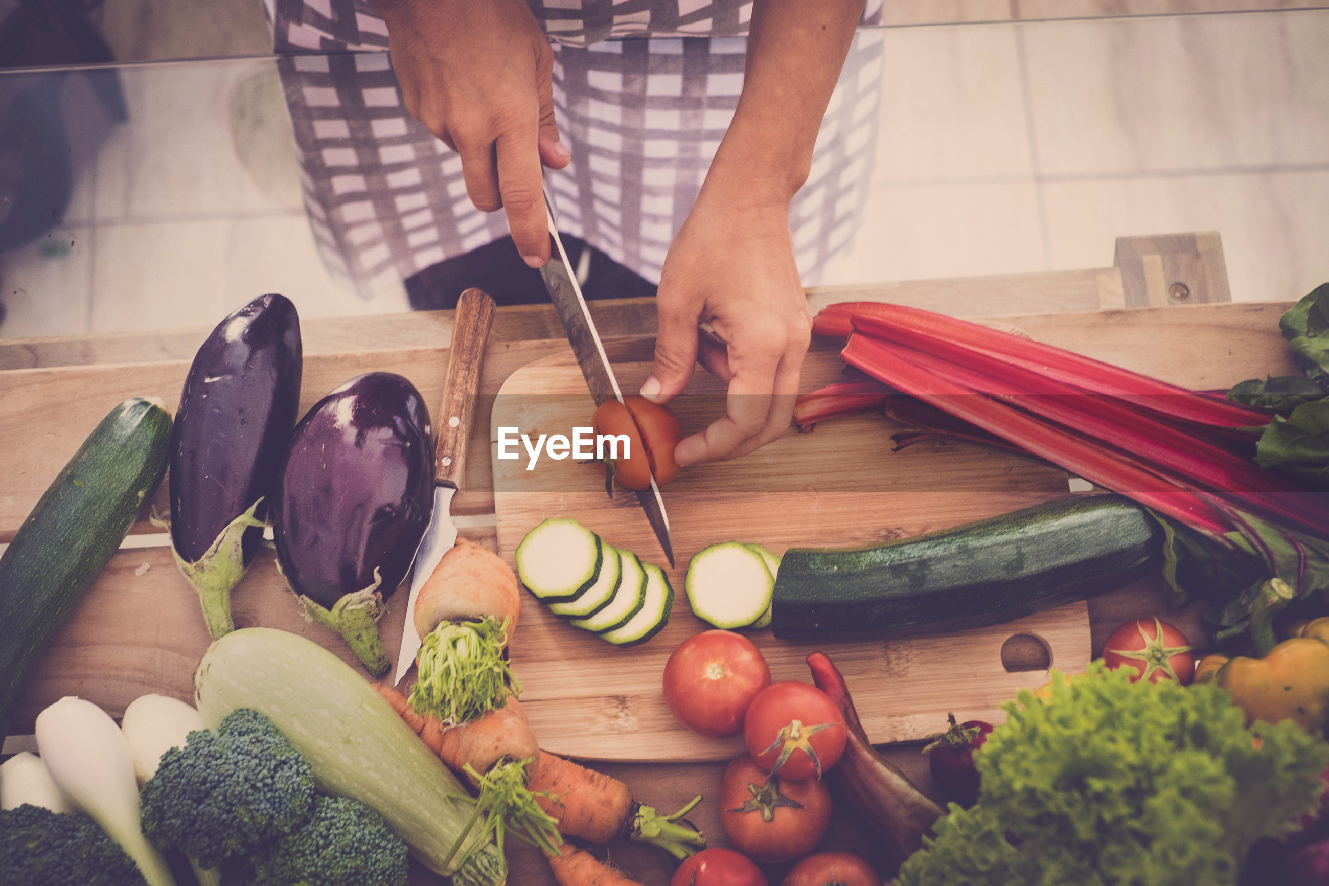 Midsection of person cutting vegetables at home