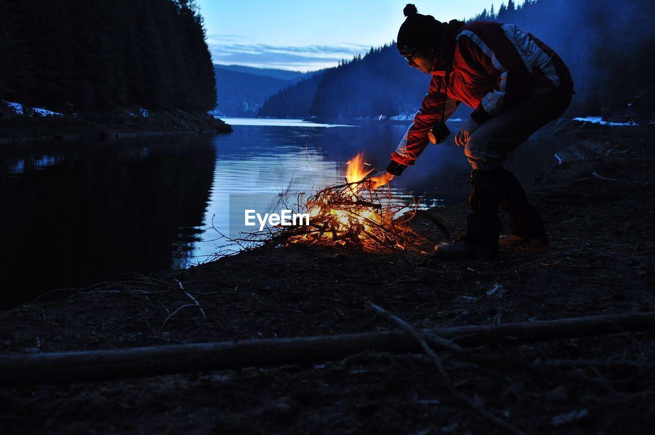 Man Burning Bonfire At Lakeshore During Dusk