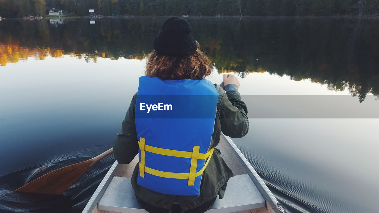 Rear View Of Man On Boat In Lake