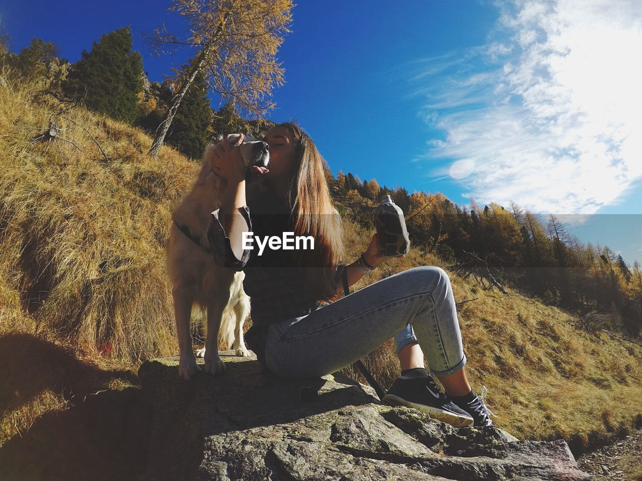 Young Woman Kissing Golden Retriever While Sitting On Rock Against Sky