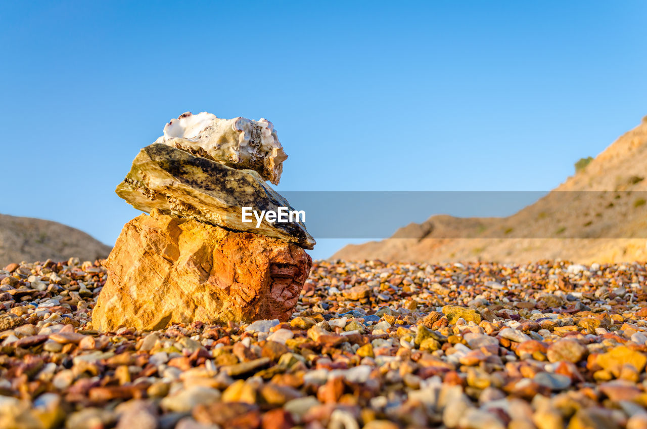 solid, rock, nature, selective focus, day, no people, rock - object, sky, clear sky, close-up, beauty in nature, blue, land, stone - object, dry, outdoors, leaf, sunlight, tranquility, plant part, surface level, pebble, change, leaves, temptation