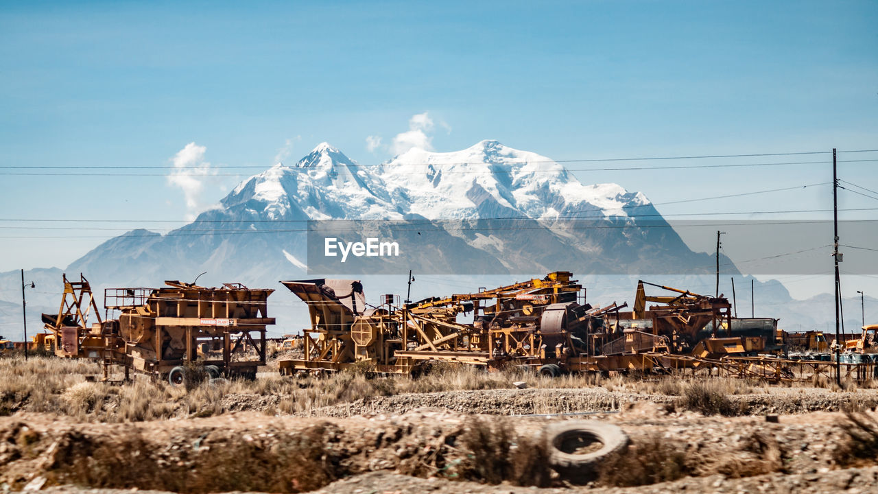 Abandoned Construction Machinery Against On Field Against Snowcapped Mountain