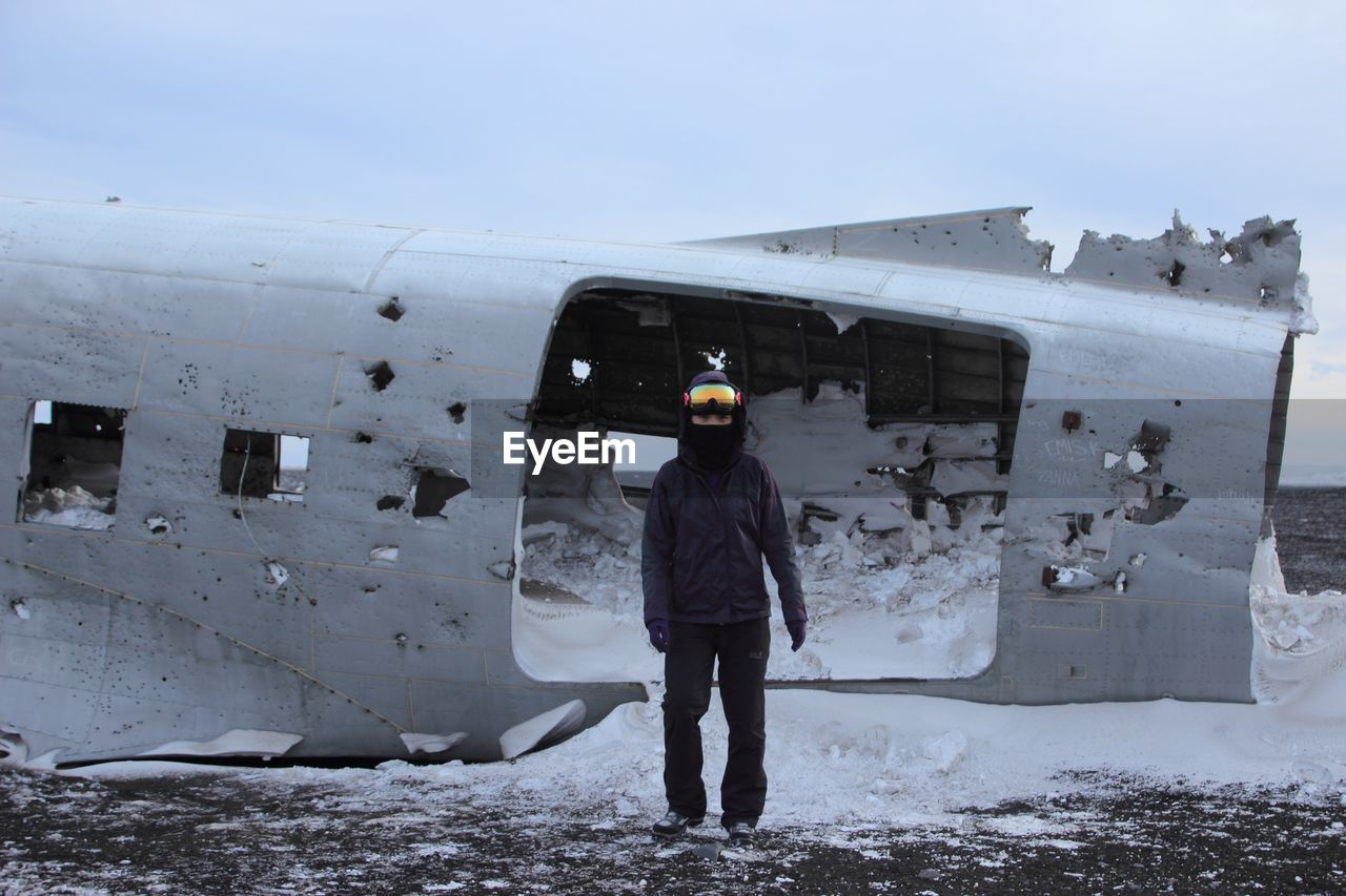 Full Length Portrait Of Person Standing By Damaged Airplane At Beach During Winter