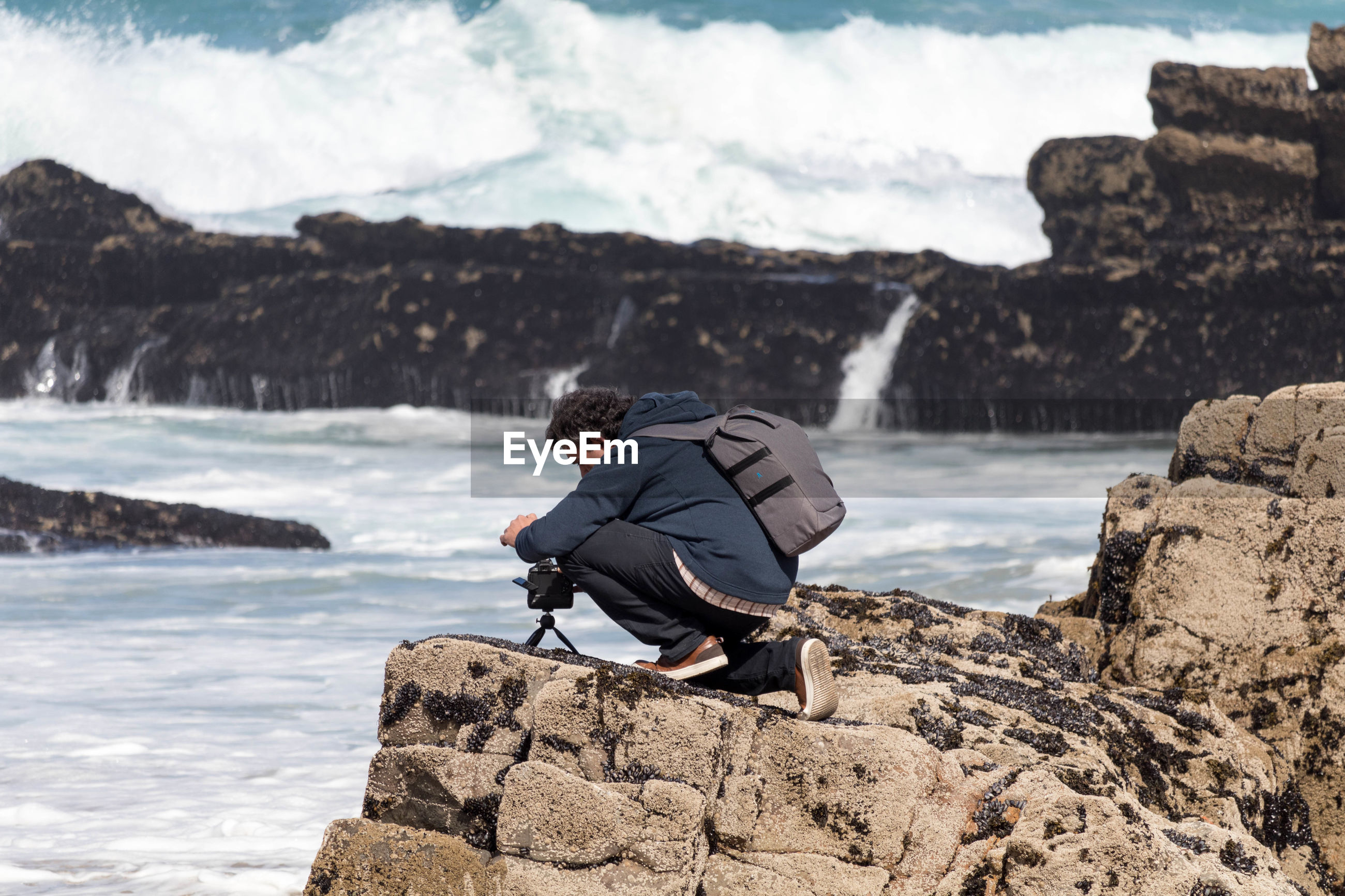 Side view of man photographing from rock at beach