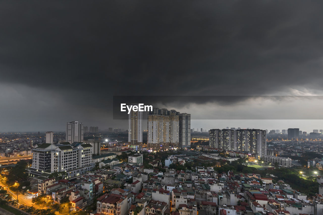Aerial view of illuminated buildings in city against strom clouds