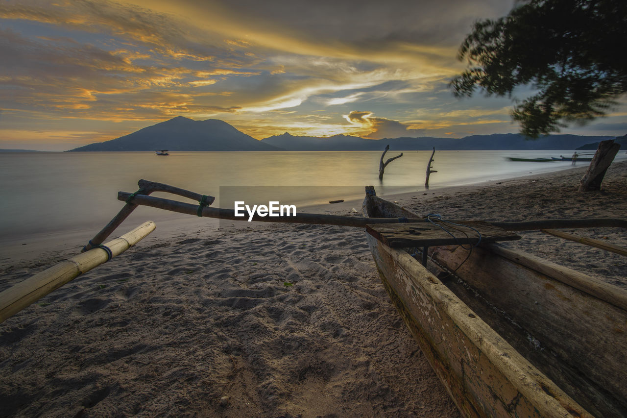 water, sky, sunset, cloud - sky, scenics - nature, beauty in nature, tranquility, tranquil scene, nautical vessel, beach, nature, sea, land, mountain, mode of transportation, transportation, wood - material, no people, non-urban scene, outdoors